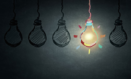 Light bulbs on dark background with one glowing Imagens