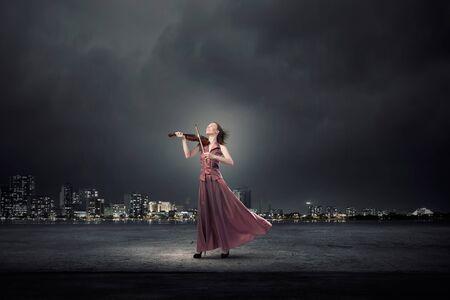 sexo femenino: Violinista femenino joven en vestido largo de color marrón noche