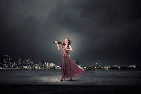 fiddles: Young female violin player in long evening brown dress