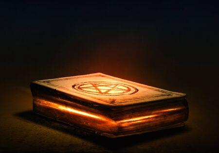 m�gica: Antiguo libro m�gico negro con luces en las p�ginas Foto de archivo