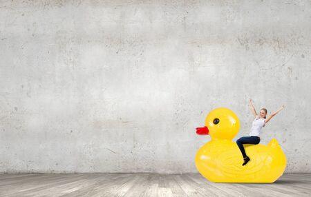 with duck: Joven empresaria feliz montando pato de goma amarillo