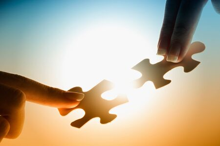 Hand aansluiten van twee puzzel gloeiende puzzelstukjes