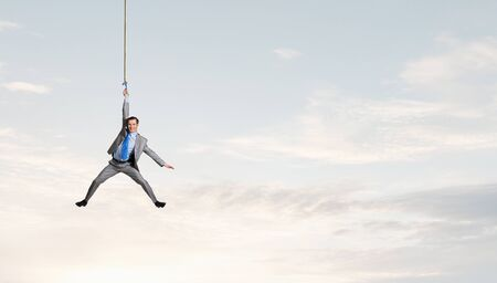 hardship: Young businessman hanging on rope high in sky
