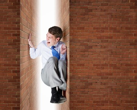 claustrophobia: Businessman under pressure between two stone walls