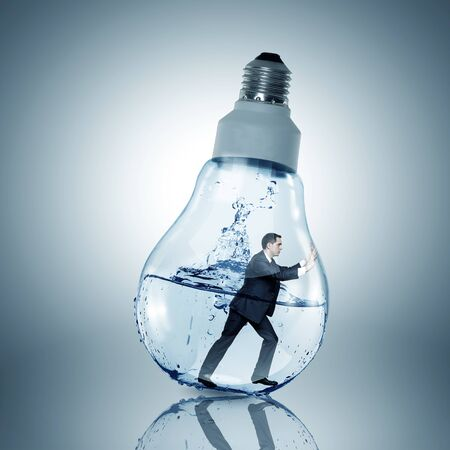 get out: Businessman inside light bulb with water trying to get out Stock Photo