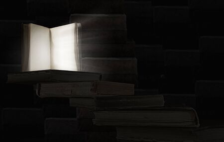 bright light: Old opened book with light coming from pages on dark background.