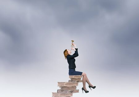 educaton: Young businesswoman sitting on pile of books proclaiming something in horn Stock Photo
