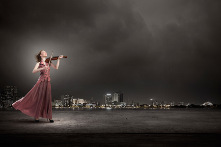 soloist: Young female violin player in long evening brown dress