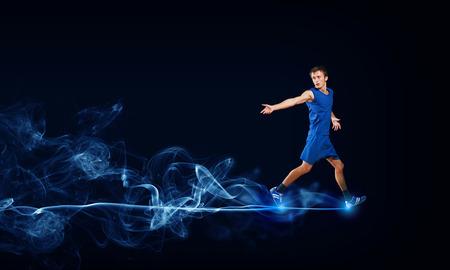 salud y deporte: Hombre corriente en ropa de deporte azul sobre fondo negro