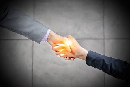 formals: Top view of a businessman and woman shaking hands in office lobby