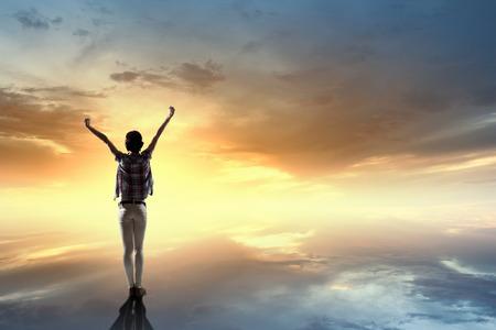Terug oog van vrolijke vrouw met handen omhoog gericht zonsopgang Stockfoto