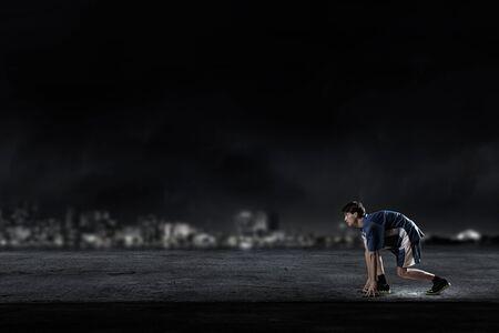 hombre deportista: Hombre del atleta en el inicio plantean sobre fondo negro Foto de archivo