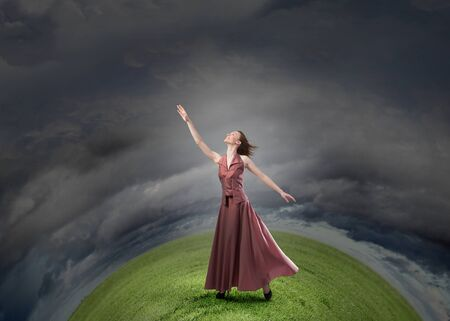 reaching hand: Young woman in in dress reaching hand to touch something Stock Photo