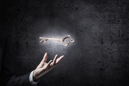 security man: Close up of human hand holding key symbol
