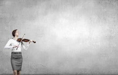 virtuoso: Young businesswoman on cement background playing violin
