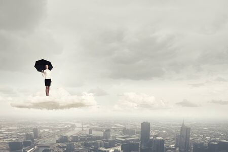 pessimist: Young businesswoman with black umbrella standing on cloud Stock Photo