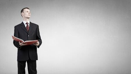 lawer: Young businessman with red book in hands Stock Photo