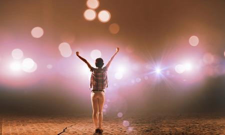 Achter mening van meisje met de handen omhoog staan in podiumlicht