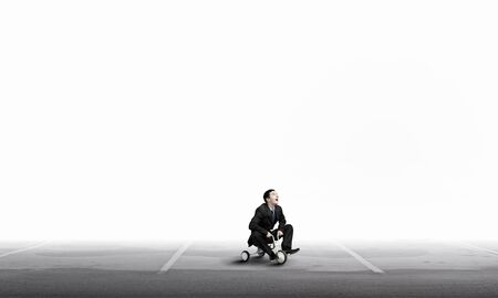 wheeled: Young funny businessman riding three wheeled bicycle