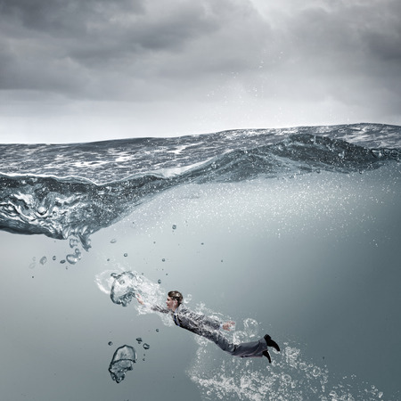 stormy waters: Young businessman in suit swimming in stormy waters
