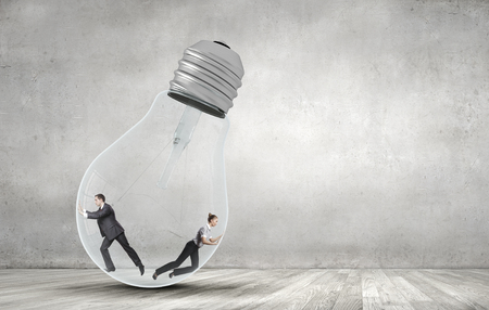 two minds: Businesswoman and businessman inside light bulb trying to get out Stock Photo