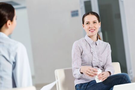 adult student: Two young women sitting at office having conversation Stock Photo