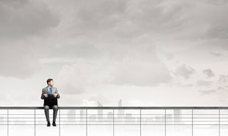 parapet: Young businessman sitting on parapet with briefcase in hands