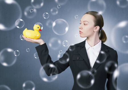 decoy: Young businesswoman holding yellow rubber duck toy in palm
