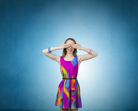 covering eyes: Young woman in multicolored dress covering eyes with hands