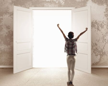 the entering: Rear view of woman with hands up entering opened door