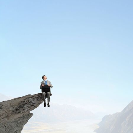 Businessman with briefcase in hands sitting on rock top
