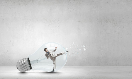 Businessman inside light bulb braking it to get out