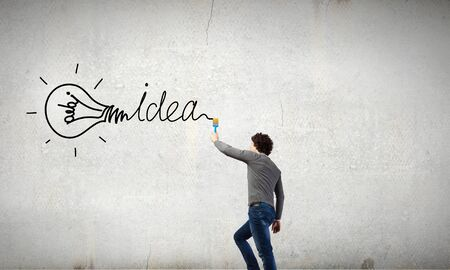 property management: Young businessman standing with back and painting word idea on wall Stock Photo