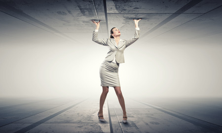 between: Young troubled businesswoman trapped between two walls Stock Photo