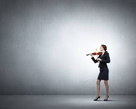 virtuoso: Young businesswoman on colorful background playing violin