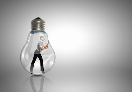 get out: Businesswoman inside light bulb trying to get out Stock Photo