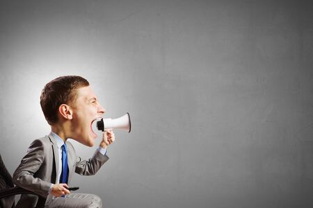 emotionally: Funny young man with big head screaming emotionally in megaphone Stock Photo