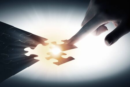 business metaphor: Hand connecting missing jigsaw glowing puzzle piece