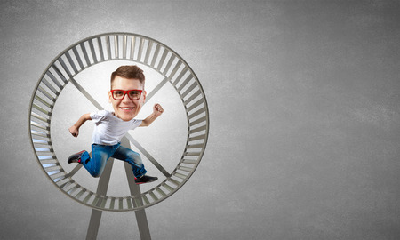 funny picture: Funny picture of running in wheel man with big head over cement background Stock Photo
