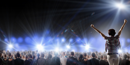 singer on stage: Back view of girl with hands up standing in stage lights