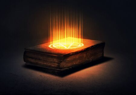 black magic: Old black magic book with lights on pages