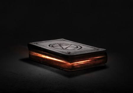Antiguo libro mágico negro con luces en las páginas Foto de archivo - 44960544
