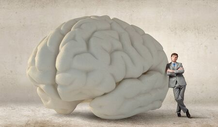 big and small: Young businessman leaning on big brain model