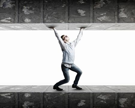 claustrophobia: Young man under pressure between two stone walls