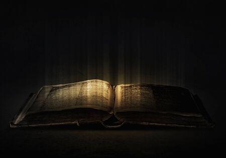 Antiguo libro mágico negro con luces en las páginas Foto de archivo - 44983044