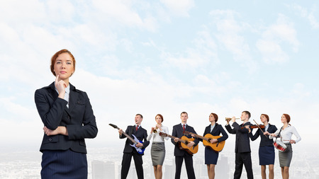 business performance: Young woman in suit playing different music instruments