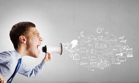 don't: Funny young man with big head screaming emotionally in megaphone Stock Photo