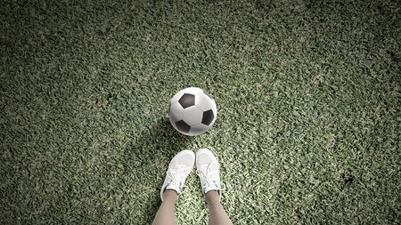 clumsy: Top view of female football player on green grass