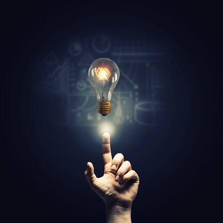 mente humana: Cerca de la mano del hombre que apunta con el dedo sobre el vidrio brillante bombilla