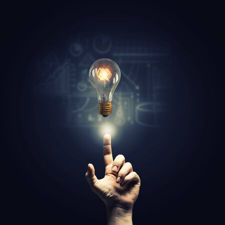 constructive: Close up of human hand pointing with finger on glass glowing light bulb